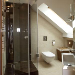 Ta łazienka na poddaszu ma bardzo nietypowy i niekorzystny kształt. Mimo to została zaaranżowana funkcjonalnie. Najniższe miejsce pod skosem wykorzystano na półki, a w najwyższym zainstalowano kabinę prysznicową.  Projekt: Piotr Gierałtowski. Fot. Tomasz Markowski.