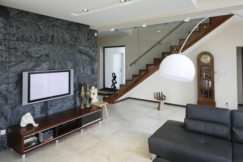 Telewizor w salonie powieszona na ścianie wyłożonej eleganckim kamieniem w czarno-szarej tonacji kolorystycznej. Projekt Piotr Stanisz. Fot. Bartosz Jarosz.