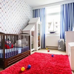 Z dominującymi w pokoju dla dziecka błękitami kontrastuje czerwony miękki dywan w stylu shaggy. Pomieszczenie to kraina fantazji ze wzorzystą tapetą i meblami w kształcie domku. Projekt: Saje Architekci, współpraca Aleksandra Nowakowska. Fot. foto&mohito.