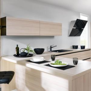 Emotion Augusto BRW to efektowne połączenie drewna o chłodnej barwie ze szlachetną czernią, gładkie powierzchnie podziału frontów odmierzone są liniami podziału korpusu – czarnymi, metalowymi uchwytami – dyscyplinującymi układ. Fot. Black Red White.