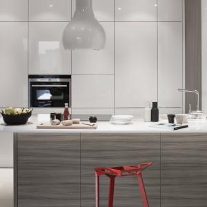 Aranżacja kuchni to połączenie matowego laminatu drewnopodobnego i klasycznej, uniwersalnej bieli w połysku. Wysoka zabudowa, blat kuchenny i panel naścienny w połysku komponują się z designerskim okapem wyspowym. Fot. ZAJC kuchnie, kuchnia Z3/020, Rafał Lipski.