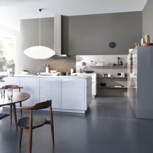 Fronty i korpusy mebli i wyspy kuchennej wykończone na połysk. Kombinacja bieli z szarością przechodzącą w beż tworzy stonowany, elegancki miks, pasujący zarówno do nowoczesnych, jak i bardziej klasycznych kuchni. Fot. Leicht, kolekcje Chiara-BG-C i Luna-C.