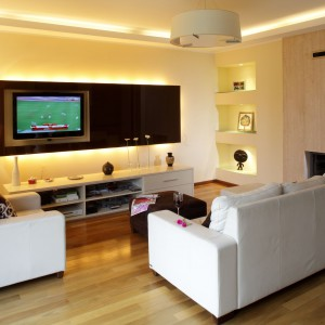 W otwartej strefie dziennej część salonową budują białe kanapy ustawione w kształcie litery L. W połączeniu z jasnymi kolorami ścian i podłogi tworzą przytulne miejsce do wypoczynku. Projekt: Piotr Gierłatowski. Fot. Tomasz Markowski.