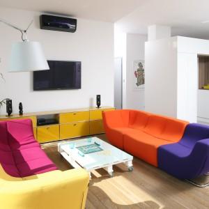 Przestronny salon połączony z kuchnią cały został zaaranżowany w bieli. Jej monochromatyczność przerywają kolorowe akcenty w postaci modułowych kanap oraz szafki po RTV. Projekt: Konrad Grodziński. Fot. Bartosz Jarosz.