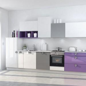 Bardzo subtelnie użyty kolor w kuchni. Stonowane biało-szare meble kuchenne delikatnie zaakcentowano wrzosowym odcieniem fioletu. Aranżacja zyskała dzięki temu kolor, nie tracąc nic ze swojego delikatnego charakteru. Fot. Nolte Kuchen, kolekcja Lux.