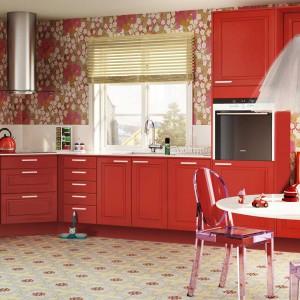 Czerwone meble, wzorzysta tapeta i biały blat kuchenny. Kuchnia utrzymana w klasycznym stylu, z frezowanymi frontami. Całość prezentuje się niezwykle oryginalnie i odważnie, a ciepły, czerwony kolor zaostrza apetyt. Fot. Ballingslov, linia Star.
