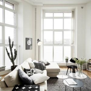Wysokie okna w salonie świetnie doświetlają wnętrze, optycznie je powiększając. Wraz z białymi ścianami i jasnymi meblami tworzą wrażenie przestronności wnętrza. Fot. Stadshem.