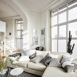 Zapierający dech w piersiach, piękny salon otwiera się na hol i schody, prowadzące na antresolę. Narożnik pełni funkcję kompletu wypoczynkowego. Przytulny klimat do jasnego, chłodnego pomieszczenia wprowadza miękki dywan i komponujące się z nim kolorystycznie poduszki. Całość utrzymano w kolorach bieli, szarości i czerni. Fot. Stadshem.