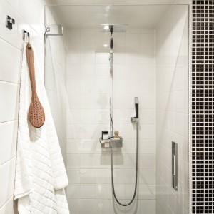 Strefę prysznica, wzorem całej łazienki, wykończono w monochromie. Ściany wykończono białymi kaflami, a podłogę kontrastującymi czarnymi płytkami. Fot. Stadshem.