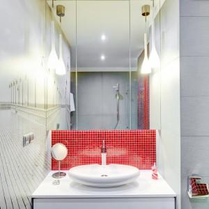 Łazienkę utrzymano w szarościach, bielach i czerwieniach. Efektowną, czerwoną mozaikę tonują szare płytki o większym wymiarze. Przestrzeń optycznie powiększa fototapeta z widokiem molo. Odbijając się w wysokim pod sufit lustrze, przedłuża perspektywę w pomieszczeniu w obu kierunkach. Projekt: Saje Architekci. Fot. foto&mohito.