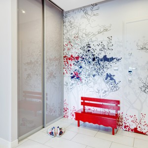 W przedpokoju na ścianie widnieje efektowna grafika w komiksowym stylu. Czarny rysunek konturów drzew ożywiają czerwone akcenty, wyglądające jak plamy po tuszu rysunkowym. Projekt: Saje Architekci. Fot. foto&mohito.