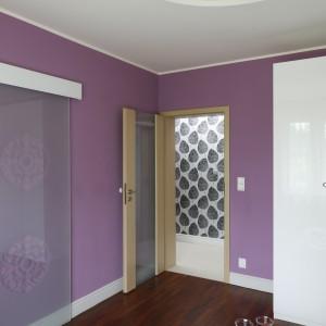 W sypialni zadbano o detale. Białe listwy przypodłogowe, prowadnica przeszklonych oraz jasna szafa równoważą kolorystycznie fiolet ścian.Fot. Bartosz Jarosz.