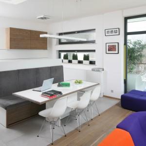 Oryginalny pomysł na jadalnię. W otwartej przestrzeni kuchni, połączonej z salonem, jadalnia zajmuje miejsce na granicy obu pomieszczeń. Delikatny, biały stół skomponowano z krzesłami w tym samym kolorze. Pomysłowym rozwiązaniem jest wyspa kuchenna, przechodząca w kanapę, zastępującą krzesła przy stole. Projekt: Konrad Grodziński. Fot. Bartosz Jarosz.