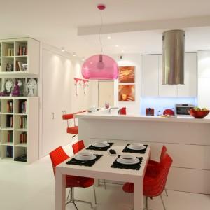 Funkcję jadalni pełni niewielki biały stolik dla 4 osób. W białym kolorze jest również podłoga, wyspa kuchenna oraz szafki kuchenne i zabudowa. Biel przełamują akcenty czerwone, w tym krzesła przy stole. Projekt: Katarzyna Mikulska-Sękalska. Fot. Bartosz Jarosz.