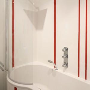 Oba elementy - wanna i parawan - mają taki sam półokrągły kształt zapewniający swobodę ruchów pod prysznicem. W czasie kąpieli można korzystać z natrysku górnego (kwadratowa deszczownica ) i słuchawki prysznicowej (wielootworowa bateria wannowa ). Projekt: Iza Szewc. Fot. Bartosz Jarosz.