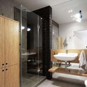 Szare, wielkowymiarowe płytki na podłodze, czarna strefa prysznica, bezramowe, proste lustro i oświetlenie w industrialnym stylu. Nie ma wątpliwości, że to łazienka dla mężczyzny! Projekt i Fot. Soma Architekci.
