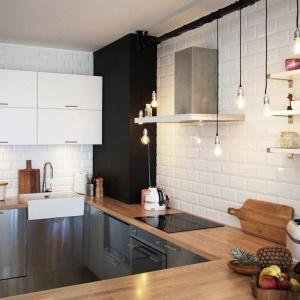 Ścianę nad blatem kuchennym wykończono pięknymi, tradycyjnymi kaflami w białym kolorze. Drewniany blat estetycznie kontrastuje ze stalowymi, połyskującymi frontami szafek i bielą na ścianach. Oświetlenie zapewniają  minimalistyczne żarówki. Projekt i Fot. Soma Architekci.