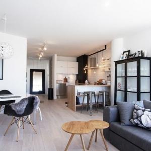 Salon, jadalnia i kuchnia tworzą wspólną, otwartą przestrzeń. Domowy klimat buduje przytulna kanapa z dekoracyjną poduszką, urokliwy stolik kawowy i stylizowana przeszklona komoda. Pięknym elementem dekoracyjnym są ażurowe abażury lamp, wiszących nad stołem jadalnianym. Projekt: Soma Architekci.