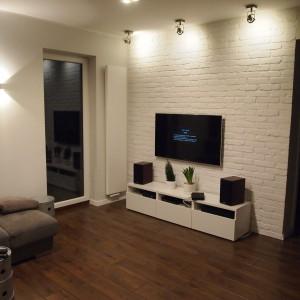 Wykorzystanie na ścianie telewizyjnej białej cegły nie stworzy konkurencji dla obrazu wyświetlającego się na monitorze. Fot. Elkamino Dom.