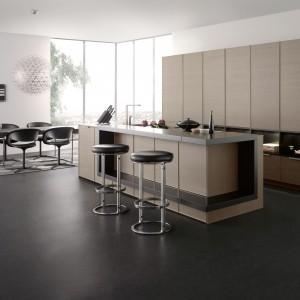 Wytworna kuchnia, w której beże skomponowano z ciemnymi szarościami i czernią. Gładkie fronty, proste linie, geometryczne formy nadają wnętrzu elegancji i nowoczesnego klimatu. Wyspa kuchenna zamknięta w oprawę z metalowej ramy. Fot. Leicht, kolekcja Classic-FS.