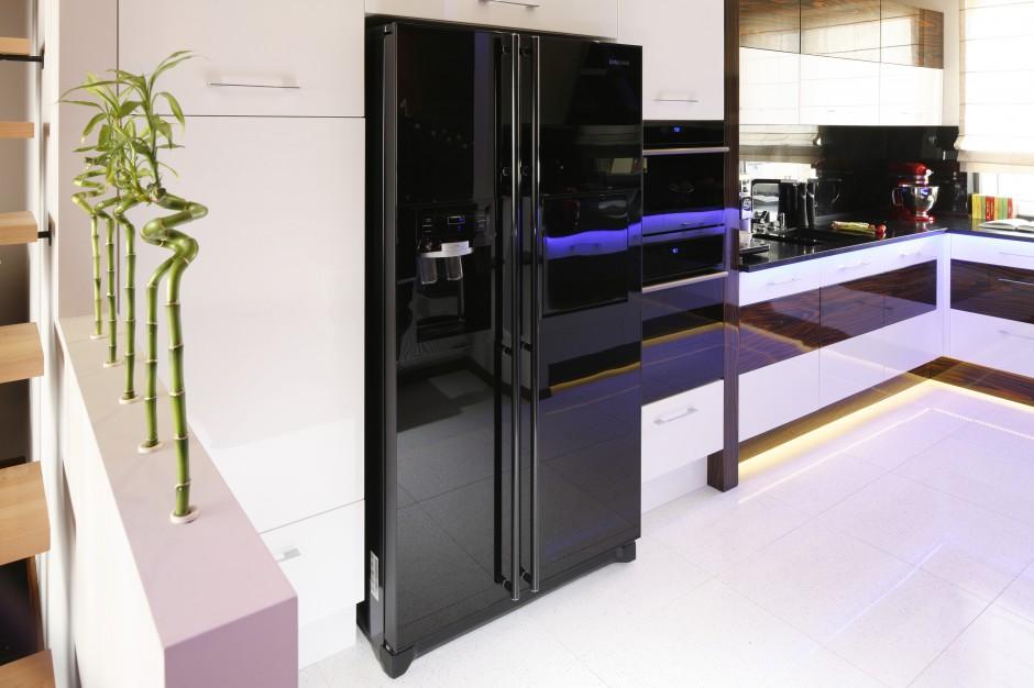 Czarna lodówka dwudrzwiowa AGD w kuchni Gdzie