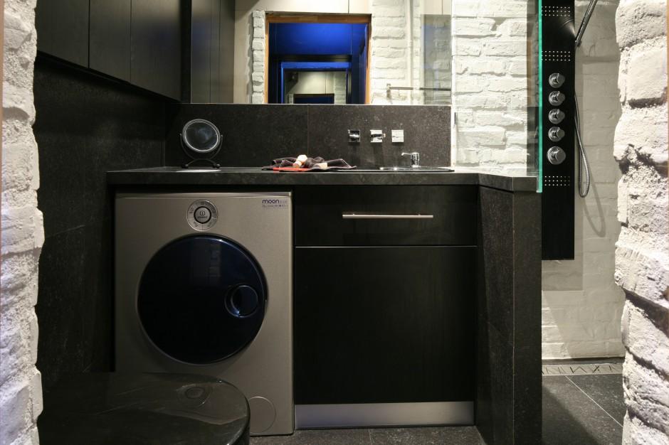 W tej urządzonej  w loftowym stylu łazience pralka pozostaje widoczna. Ulokowana została pod blatem umywalkowym i sąsiaduje bezpośrednio  z szafką. Model pralki został dobrany kolorystycznie do stylu łazienki. Projekt: Dominik Respondek. Fot. Bartosz Jarosz.