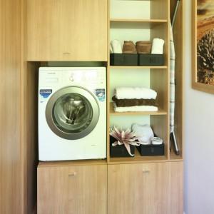 Metraż łazienki umożliwił wygospodarowanie niewielkiej przestrzeni na pralnię. Zabudowa pralki została zaplanowana, tak aby zmieściły się tu wszystkie detergenty, a nawet deska do prasowania. Pralna została ulokowana nietypowo, ale bardzo funkcjonalnie na pewnej wysokości. Dzięki temu nie trzeba się schylać podczas ładowania pralki i wyjmowania prania.  Projekt: Małgorzata Błaszczak. Fot. Bartosz Jarosz.