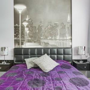 W sypialni również postawiono na intensywne barwy - tym razem prym wiodą fiolety i fuksja. Całość otrzymała błyszczące wykończenie. Połyskujące lampki nocne, czarne szafki nocne wykończone na połysk oraz zdjęcie rozświetlonej metropolii nadają wnętrzu eleganckiego charakteru. Przestrzeń optycznie powiększa duża tafla lustra. Projekt: Saje Architekci. Fot. foto&mohito.