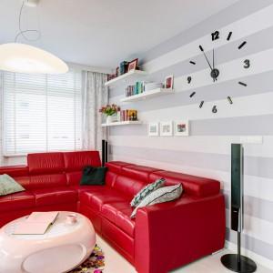 Czerwony narożnik stanowi efektowny akcent kolorystyczny w przestrzeni dziennej. Szara tapeta w pasy na ścianie za meblem wypoczynkowym tonuje żywe barwy, nadając aranżacji subtelności. Projekt: Saje Architekci. Fot. foto&mohito.
