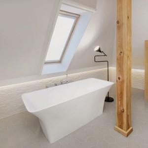 Na poddaszu zlokalizowano strefę dla gości. Do ich dyspozycji jest między innymi piękna, jasna łazienka, w której królują biel, szarość i ciepłe drewniane akcenty. Wolno stojąca wanna z widokiem na niebo przeistacza łazienkę w salon kąpielowy. Projekt: Razoo Architekci. Fot. Meluzyna Studio.