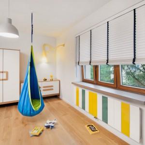 W pokoju dziecięcym zawieszono huśtawkę-siedzisko. Jest nie tylko kolorowa, ale przede wszystkim zapewnia masę frajdy. Barwnymi akcentami są również kolorowe wstawki grzejnika płytowego i fantazyjna lampa w rogu pomieszczenia. Projekt: Razoo Architekci. Fot. Meluzyna Studio.