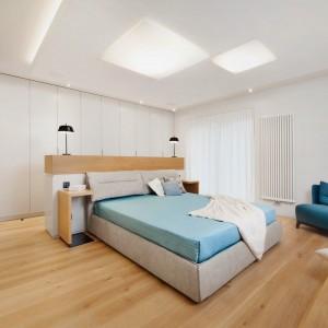 Przestronna sypialnia małżeńska zachwyca jasnymi barwami i oszczędnością aranżacji.  Przytulny charakter przestrzeni do spania i wypoczynku budują tutaj dekoracyjne tekstylia, ale również zastosowane bez zbędnej przesady. Wysoka zabudowa za łóżkiem pozwala uporządkować wnętrze. Wezgłowie stanowi jednocześnie półkę pod lampki nocne - zrezygnowano zatem z dodatkowych szafek. Ascetyczny charakter przełamuje przytulny tapicerowany fotel. Połączenie bieli  i beżów ożywiają turkusowe akcenty kolorystyczne. Projekt: Razoo Architekci. Fot. Meluzyna Studio.