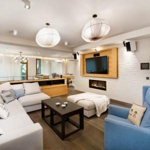TV w salonie zlokalizowano na drewnianym panelu. Efektownie kontrastuje on z biała cegłą na ścianie. Żarzący się w kominku ogień, w połączeniu z fakturą cegły tworzy niezwykle klimatyczne połączenie. Projekt: Razoo Architekci. Fot. Meluzyna Studio.