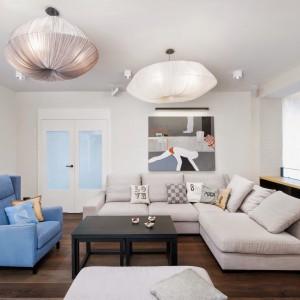 W salonie, wzorem innych pomieszczeń, intensywniejszy akcent kolorystyczny utrzymano w odcieniach błękitu. Niebieski fotel uzupełnia duży, szary narożnik i puf w zestawie. Projekt: Razoo Architekci. Fot. Meluzyna Studio.