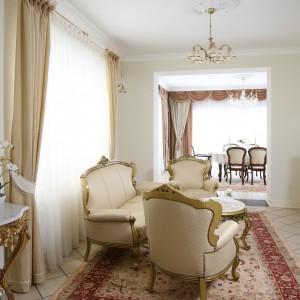 Stylizowane meble nadają wnętrzu iście królewski wygląd. Charakter salonu wzmacniają złocone lampy oraz dekoracje. Projekt: Małgorzata Goś. Fot. Bartosz Jarosz.