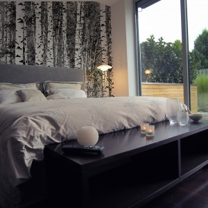 Dekoracja ściany w formie wielkoformatowej tapety nawiązuje do widoku z przestronnych okien sypialni. Dzięki niej udało stworzyć się wnętrze, które współgra z naturalnym otoczeniem domu. Fot. Art of wall.