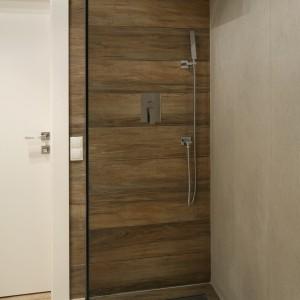 Strefa prysznica urządzona jest minimalistycznie. Ciekawie też dobrano wyposażenie i materiały. Drewnopodobne płytki stanowią tło dla nowoczesnych form armatury, do których dopasowuje się pod względem stylu także stalowy ruszt odpływu. Projekt: Dominik Respondek. Fot. Bartosz Jarosz.