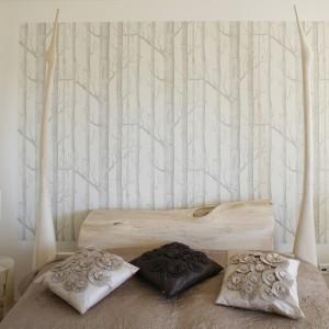 Sypialnia inspirowana naturalnymi materiałami. Bogato zdobione łóżko, stoliki nocne z widocznymi rysunkami drewna korespondują z tapetą umieszczoną na fragmencie ściany za łóżkiem. Projekt: Marta Kruk. Fot. Bartosz Jarosz.