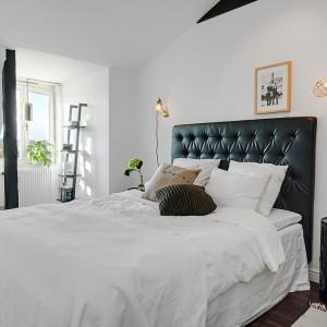 Czarne, tapicerowane łóżko z wysokim zagłówkiem tworzy ciekawy duet z jasnymi ścianami, które przełamano czarnymi elementami. Fot. Alvhem Makler.