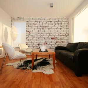 Biała cegła przyprószona nieco pyłem czasu to idealne tło dla stonowanej aranżacji salonu. Fot. Dekornik.