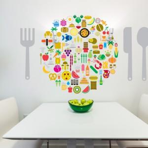 Jak lepiej ozdobić ścianę w jadalni, jeśli nie spożywczym motywem? Fantazyjna naklejka w kształcie koła, które tworzą barwne smakołyki. Uzupełniają ją naklejki w kształcie sztućców. Fot. Pixers.