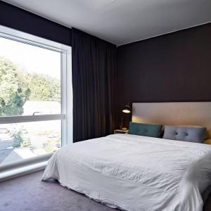 Czarne ściany w sypialni równoważą jasne meble i wykładzina podłogowa. Fot. Stadshem.