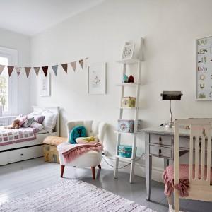 W pokoju dziecięcym, wzorem całego mieszkania, dominuje biel. Ożywiają ją kolorowe akcenty: różowe tkaniny i seledynowa poduszka z kotem. W przestrzeni, oprócz łóżka zlokalizowanego pod oknem, zmieszczono również praktyczne biurko - niezbędnik małego ucznia. Pod łóżkiem wygospodarowano miejsce na duże, pojemne szuflady. Fot. Stadshem.
