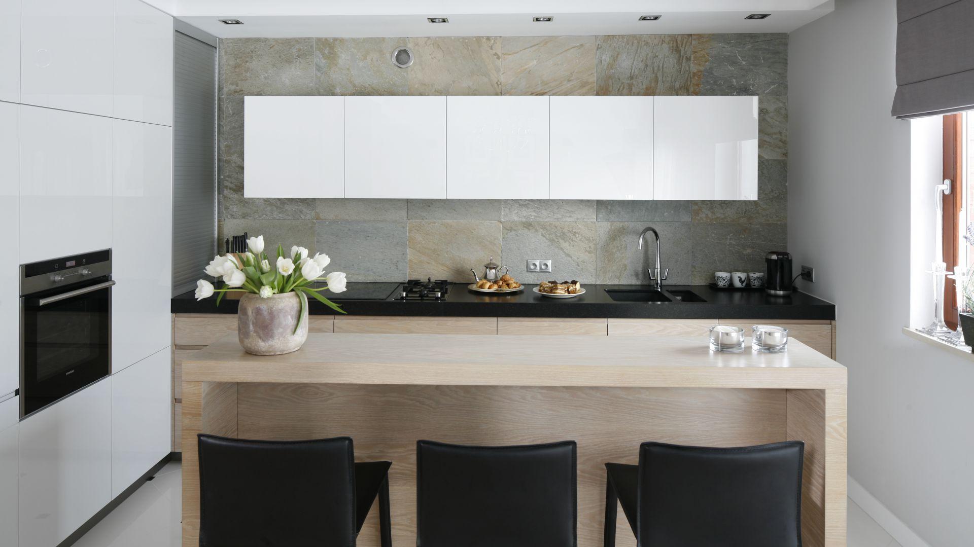 Melanżowa ściana nad blatem ułożona z dekoracyjnego kamienia sprawia, że kuchnia zyskuje elegancki, a zarazem ekologiczny wygląd. Projekt: Magdalena Smyk. Fot. Bartosz Jarosz.