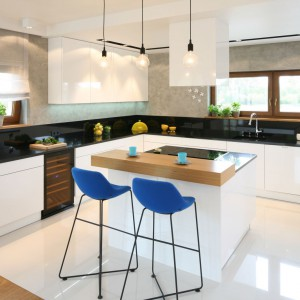 Naturalny charakter kuchni w kolorach ziemi podkreślają krzesła barowe w chabrowym kolorze, ożywiając jednocześnie aranżację. Projekt: Małgorzata Galewska. Fot. Bartosz Jarosz.