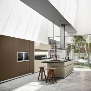 Pomysł na nowoczesną kuchnię w barwach ziemi: brązowe szafki, beżowa wyspa i podłoga z płytek w kolorze naturalnego kamienia. Fot. Snaidero.