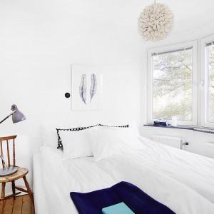 W sypialni znajduje się piękny wykusz z trzema dużymi oknami bez szprosów, które zapewniają bogaty dostęp światła do pomieszczenia. Odbijane jest ono przez dominującą we wnętrzu biel, która optycznie powiększa przestrzeń pokoju. Fot. Vastanhem.