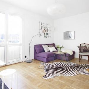 Podłogę w salonie pokryto dębowym parkietem, ułożonym w klasyczny wzór. Jasny kolor drewna ociepla wizualnie wnętrze, a naturalny materiał nadaje mu elegancji. Fot. Vastanhem.