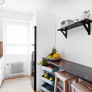 Na tle białych ścian w kuchni, zawisły wyeksponowane przez kontrast barw, proste czarne półki. Duet czerni i bieli nadaje im eleganckiego charakteru, a prosta forma tworzy wrażenie lekkości, nie przytłaczając wnętrza. Fot. Vastanhem.