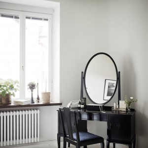 W narożniku sypialni ustawiono stylową toaletkę. Czarny mebel jest efektownie wyeksponowany na tle jasnych, szarych ścian. Barokowa stylistyka wprowadza do wnętrza element klasycznej elegancji. Fot. Stadshem.